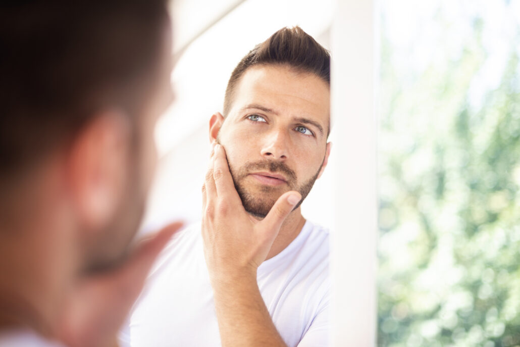 anti aging tips for menClose-up shot of a handsome young man with towel in his neck admiring looking at his face in the bathroom mirror.