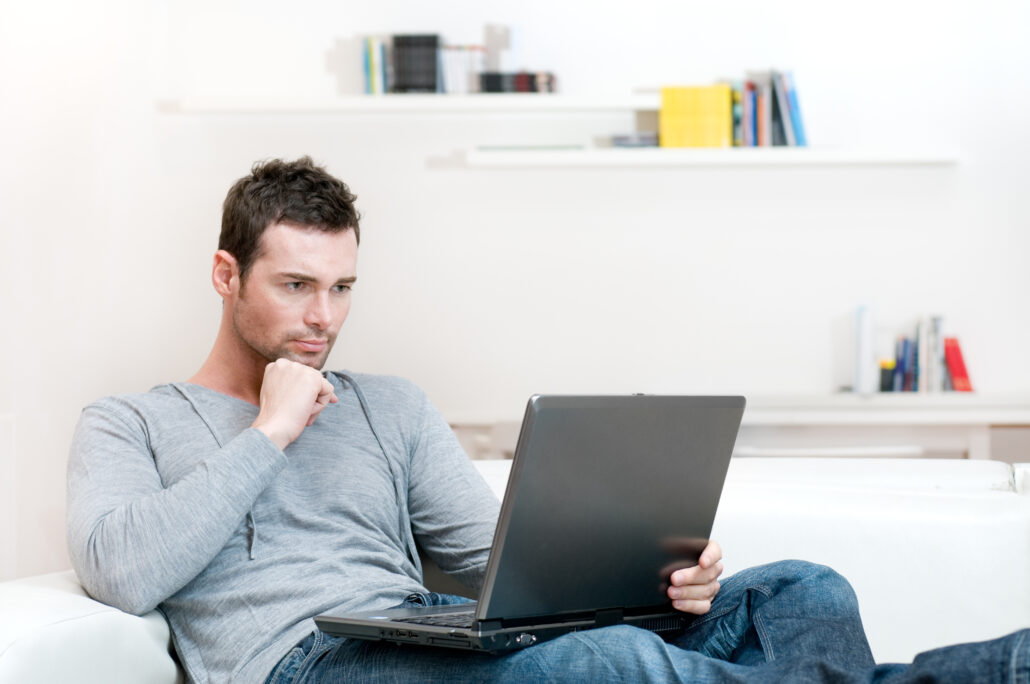Man working on laptop at determining questions to ask his doctor about testosterone